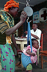 A mother put her baby on the weight scale. The nurse will then orient the mother and her child to the right child health service at the Mucaca health centre, district of Burera, Rwanda
