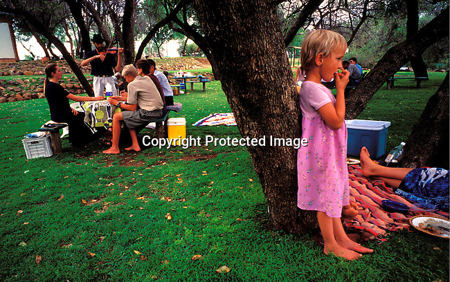 DIPOAFR00078.Culture Afrikaners Mart-Mari , age 5, having a picnic with her family and eating traditional Afrikaner food during a holiday at the camping along the Orange River. They live in the all white town of Orania, South Africa where no colored och black people are allowed. Orania is a community of about 600 people where the residents are trying to to preserve Afrikaner culture and language..Photo: Per-Anders Pettersson/ iAfrika Photos.