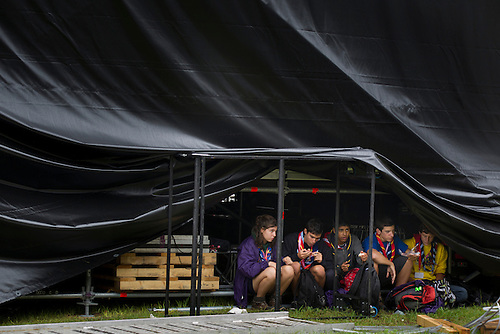 Scouts hide under a stage to not get wet in the rain. Photo: Magnus Fröderberg/Scouterna