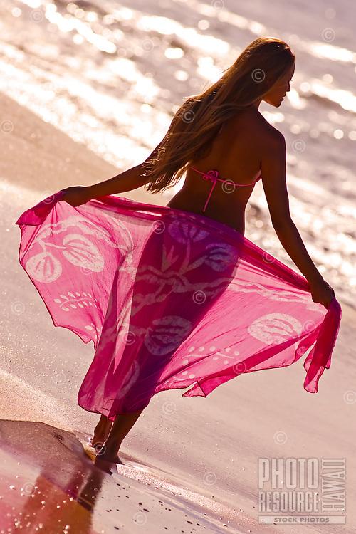A girl holds out a pink sarong backlit, at Big Beach, Makena, Maui.