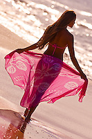 A girl holds out a pink sarong backlit, at Big Beach, Makena, Maui.