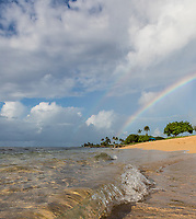 Towards sunset, a rainbow starts to appear over another, seen from the beach at Hale'iwa Ali'i Beach Park, North Shore, O'ahu.