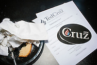 Campaign materials lay on a table while Texas senator and Republican presidential candidate Ted Cruz speaks to a crowd at a business round-table at the Draft Sports Bar and Grille in Concord, New Hampshire.
