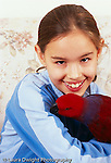 closeup portrait of 11 year old girl holding pet parrot vertical