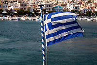 Greek flag waving in the wind in front of Pothia or Pothaia port, Kalymnos, Greece