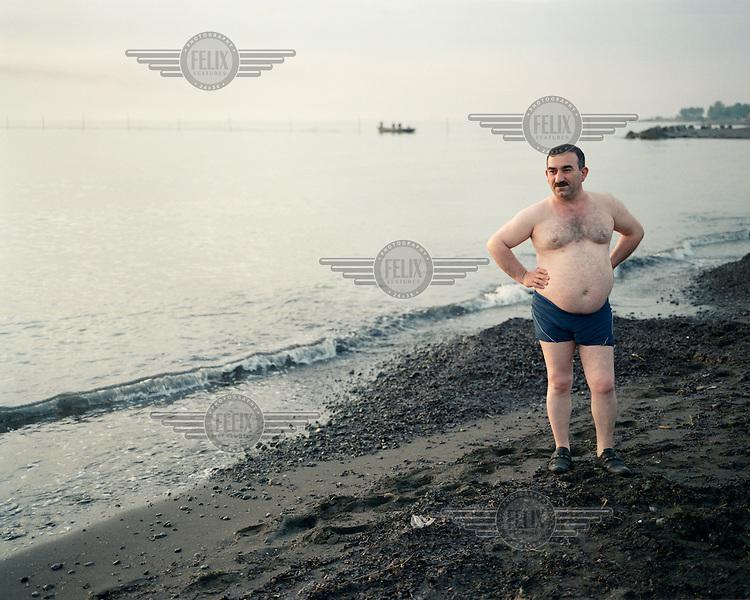 An Azeri man pauses on his morning walk along the Caspian Sea shore.