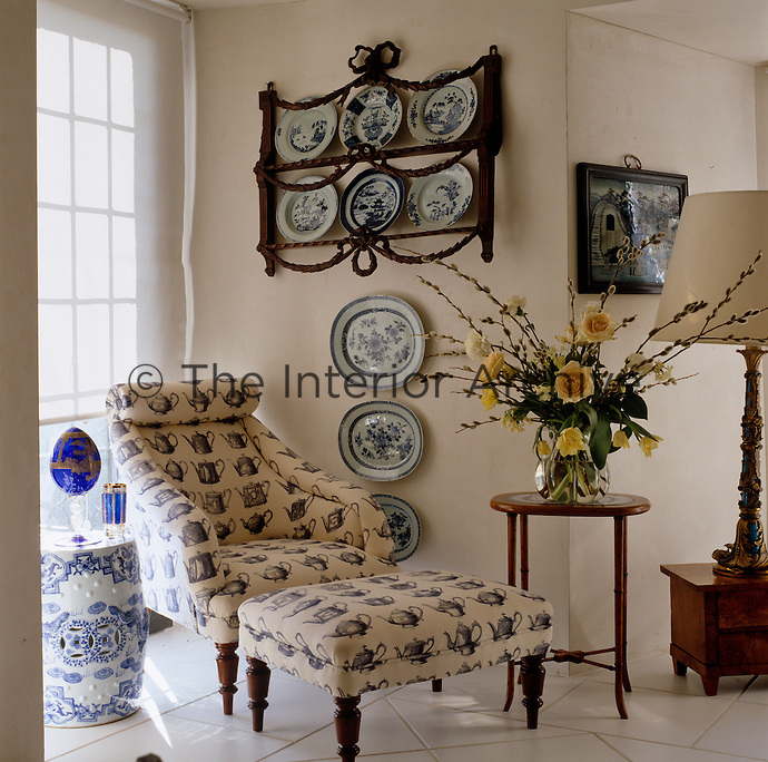 A carved plate rack displays blue and white plates above an armchair and footstool upholstered in a blue and white fabric