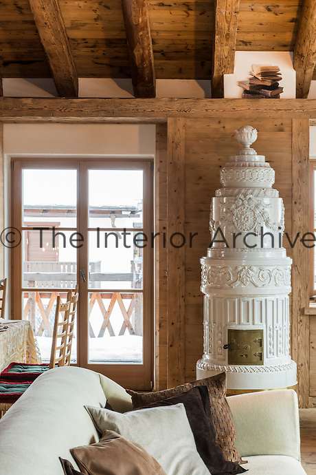 The living room of the ski chalet is kept warm by the traditional Austrian white ceramic stove.