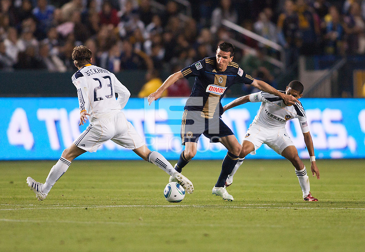Philadelphia Union forward Sebastien Le Toux (C-9) attempts to move through LA Galaxy midfielder David Beckham (L-23) and defender Sean Franklin (R-5). The LA Galaxy defeated the Philadelphia Union 1-0 at Home Depot Center stadium in Carson, California on  April  2, 2011....