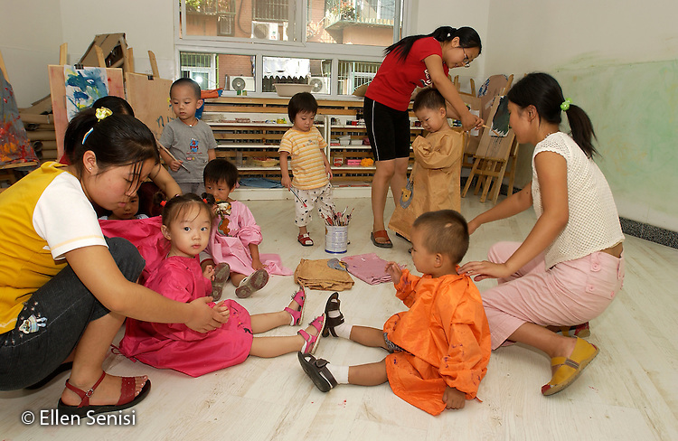 Beijing, China.Little Oak Children's House: private day care center and private elementary school..Teacher and aides dress students in smocks for painting activity..© Ellen B. Senisi