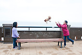 Lima, Peru. Miraflores district, Larcomar Mall. Two young girlfriends (Peruvian) toss a stuffed animal back and forth on a bench at a viewpoint over the Pacific Ocean. No MR. ID: AL-peru.
