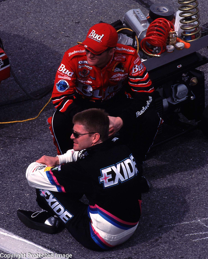 NASCAR driver Dale Earnhardt Jr. (in red) and Jeff Burton sit together as they await there turns to attempt to qulify for the Daytona 500 at Daytona International Speedway 2/13/00.(Photo by Brian Cleary)