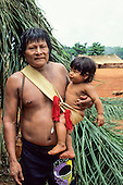 A-Ukre Village, Brazil. Kubenikaiti, a Kayapo man, holding his son in a woven palm sling.  Xingu Indian Reserve.