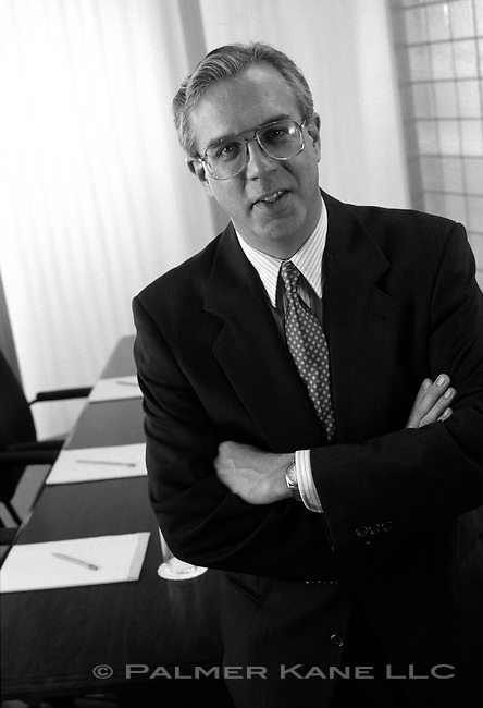 Black and white portrait of executive standing in front of conference table