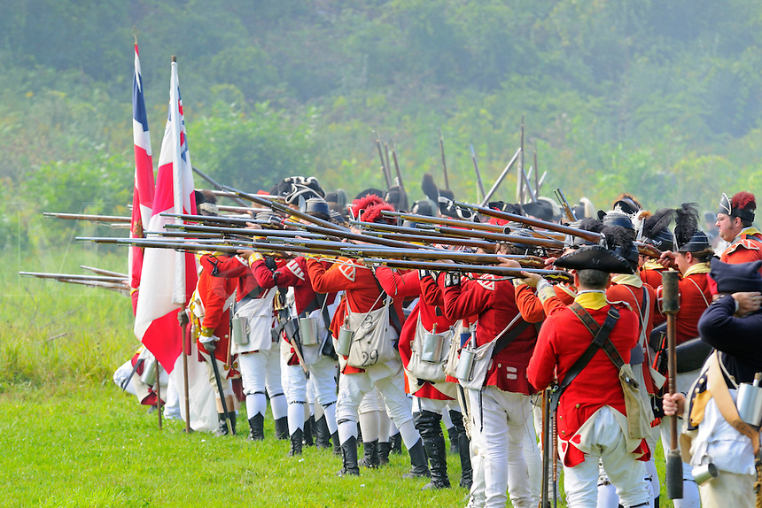 British redcoats of His Majesty's Regiments of Foot prepare to fire muskets during a Revolutionary War re-enactment at Fort Ticonderoga, New York, USA.