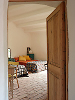 View into the guest bedroom with a pair of  double beds with patterned crocheted blankets
