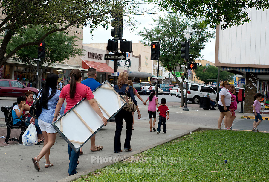 Shoppers walk Main Street in downtown McAllen, Texas, Saturday, April 3, 2010. Downtown McAllen stores don't sell designer or name brand items, but still reach a wide customer base for McAllen residents and visiting Mexican tourists. ...PHOTO/ Matt Nager
