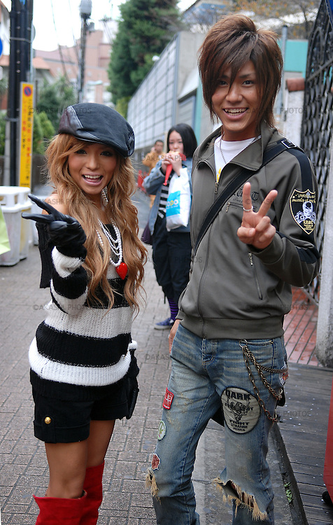 Girl and boy posing on Takeshita Street wearing Japanese fashion clothes. Harajuku. Tokyo.