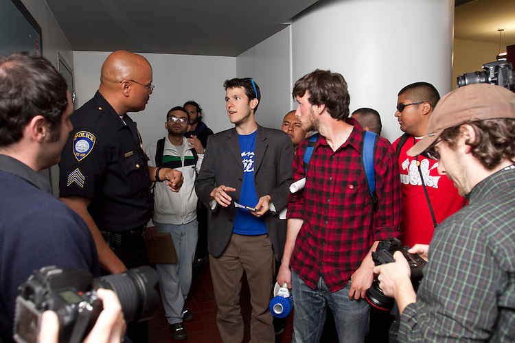 Santa Monica College Associated Students president Harrison Wills talks to campus police before demonstrators rushed police during an SMC Board of Trustees meeting April 3. 2012 at Santa Monica College in Santa Monica, Calif.  Around 54 protestors objecting to SMC's new two tier pay system that raises tuition on special core classes like Math and English marched  to the doors of the board room where police tried to maintain order and allow students who had arranged prior seating into the meeting. A lengthy discussion by members of the protest waffled between an orderly entry and anger that the Board had not chosen a larger venue to accommodate all. The flashpoint of confrontation occurred when ticketed students began entering and another group rushed the police at the door resulting in a pushing match between protestors and police that ended when pepper spray was used to clear the crowd. Two students were transported to hospital, five treated on scene for pepper spray irritation and many more were mildly affected including people in the boardroom. (Photo: Gerard Burkhart 818-207-0273)