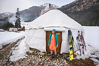 A woman skier stands outside her yurt wrapped in a towel, ready to go hot tubbing in Kyrgyzstan