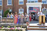 Wantagh, New York, USA. July 4, 2016. Miss Wantagh contestants, past and present, bow their heads and pause for moment of silence in honor of American military members at start at the 60th Annual Miss Wantagh Pageant crowning ceremony, an Independence Day tradition on Long Island. Below flag in dark dress is Ella Stevens, the Miss Wantagh Pageant Coordinator. Since 1956, the Miss Wantagh Pageant, which is not a beauty pageant, crowns an area high school student based mainly on academic excellence and community service.