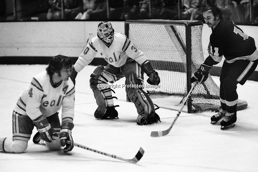 Seals vs Los Angeles Kings 1975, Kings #11 Mike Corrigan shot on Gary Simmons, and Bob Stewart.<br />(photo/Ron Riesterer)