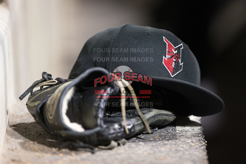 An Indianapolis Indians hat rests on top of a glove in the visitors dugout during the game against the Charlotte Knights at BB&T BallPark on June 20, 2015 in Charlotte, North Carolina.  The Knights defeated the Indians 6-5 in 12 innings.  (Brian Westerholt/Four Seam Images)