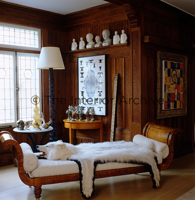 A white bear skin is draped over a 19th century American chaise longue in the panelled living room and enhanced by a collection of porcelain