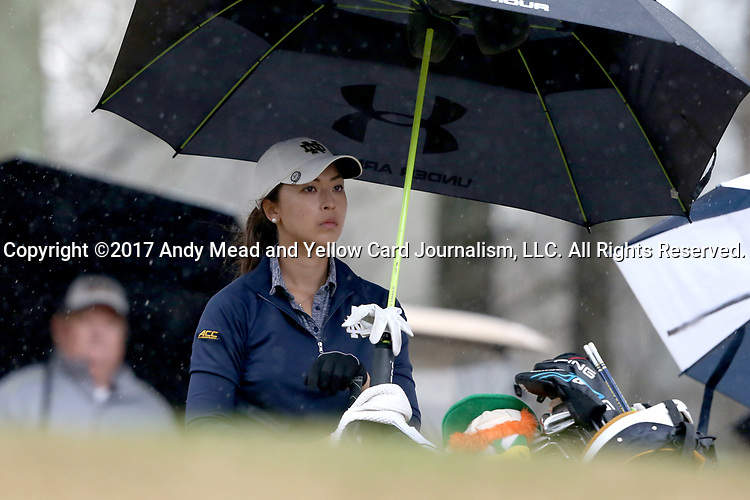 BROWNS SUMMIT, NC - MARCH 31: Notre Dame's Mia Ayer waits under an umbrella to tee off on the 11th hole. The first round of the Bryan National Collegiate Women's Golf Tournament was held on March 31, 2017, at the Bryan Park Champions Course in Browns Summit, NC. A waterlogged course eventually suspended play.