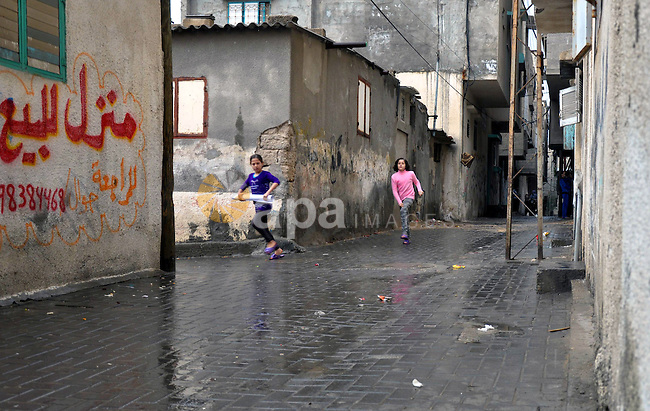 Palestinian children walk in a flooded street during a rainy day at al-Shati refugee camp, the third largest in the Palestinian Territories, in Gaza City on November 11, 2013. Photo by Mohammed Talatene
