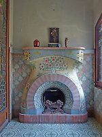 A small sitting room on the top floor is dominated by an Art Nouveau style fireplace, decorated in mosaic tiles by Louis Bru