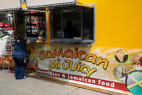 Overweight woman ordering from a Jamaican food truck in downtown Vancouver, BC, Canada