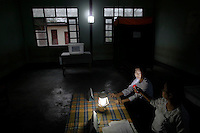 An election official uses a torch light to check the clock before opening a polling station in Kawhmu township where Aung San Suu Kyi stands as a candidate in parliamentary by-elections April 1, 2012. Myanmar votes on Sunday in its third election in half a century, a crucial test of its nascent reform credentials that could propel opposition leader Aung San Suu Kyi into parliament and convince the West to end sanctions. REUTERS/Damir Sagolj (MYANMAR)