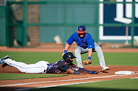 Northwest Arkansas Naturals outfielder Khalil Lee (24) safely slides back to first under the tag attempt from Midland RockHounds infielder Mikey White (5) on May 4, 2019, at Arvest Ballpark in Springdale, Arkansas. (Jason Ivester/Four Seam Images)