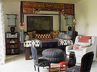 In a guest bedroom an antique opium bed from Bali is dressed with an African quilt and pillows covered in Ikat prints and Balinese sarong fabrics