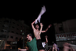 Palestinians celebrate in Gaza City on May 30, 2014, after Palestine qualified for their maiden Asian Cup appearance with a 1-0 win over injury-hit Philippines in the final of the AFC Challenge Cup in Maldives. Photo by Ezz Zanoun