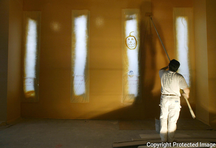 Painter Quanz Touz uses a roller to paint the walls inside the North Section room of McCaw Hall. The North and South Rooms will be used for private parties, receptions and meetings. Someone painted a pumpkin on the window coverings as a Halloween decoration. The McCaw Hall is scheduled to open June 28, 2003. Jim Bryant Photo