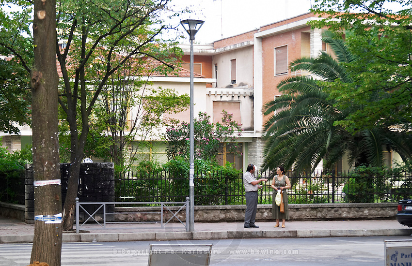 A man and a woman talking on the street in front of the old dictator's palace. Street scene from the part of the city called The Block that used to be reserved for party dignitaries during the communist era. Tirana capital. Albania, Balkan, Europe.