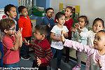 Preschool 2-3 year olds music time musical activity group jumping and dancing to song with hand gestures