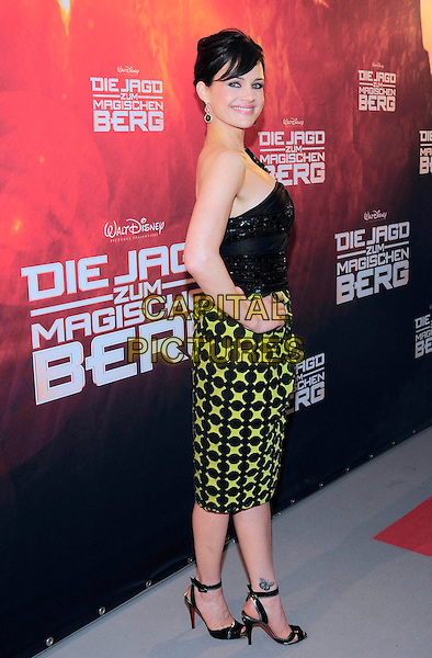 "CARLA GUGINO.Premiere for ""Race to Witch Mountain"", Astor Film Lounge, Berlin, Germany..March 31st, 2009.full length black one shoulder top green skirt dress hand on hip pattern beads beaded tattoo ankle butterfly .CAP/PPG/NK.©Norbert Kesten/People Picture/Capital Pictures"