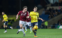 Chris Maguire of Oxford United plays a pass under pressure from John-Joe O'Toole of Northampton Town during the Sky Bet League 2 match between Oxford United and Northampton Town at the Kassam Stadium, Oxford, England on 16 February 2016. Photo by Andy Rowland.