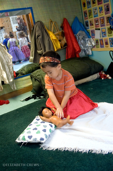 "Berkeley CA Boy, four-years-old, dresssed up and playing ""mom"" with dolls at preschool"