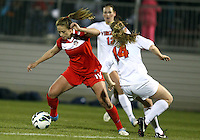 BOYDS, MARYLAND - April 06, 2013:  Caroline Miller (10) of The Washington Spirit pushes the ball away from Kristen McNabb (14) of the University of Virginia women's soccer team in a NWSL (National Women's Soccer League) pre season exhibition game at Maryland Soccerplex in Boyds, Maryland on April 06. Virginia won 6-3.