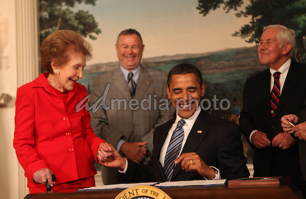 Washington, DC - June 2, 2009 -- United States President Barack Obama gives former first lady Nancy Reagan a ceremonial pen at the signing of the Ronald Reagan Centennial Commission Act in the Diplomatic Reception Room of the White House on Tuesday, June 2, 2009 .  In the background at left is U.S. Representative Dana Rohrabacher (Republican of California) and U.S. Senator Richard Lugar. Photo Credit: Dennis Brack/CNP/AdMedia