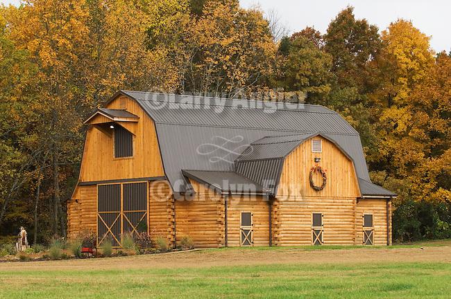 Newly built log barn with autumn wreath, rural Tennessee.