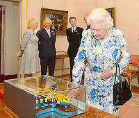 10 June 2016 - London, England - Queen Elizabeth II looks at a replica canoe of the one she and Prince Philip Duke of Edinburgh arrived by during their visit to Tuvalu in 1982, which was presented to her by presented to her by Governor General Sir Iakoba Italeli of Tuvalu ahead of a lunch at Buckingham Palace in London. Also pictured Camilla Duchess of Cornwall and Prince Charles Prince of Wales in the background. Photo Credit: ALPR/AdMedia