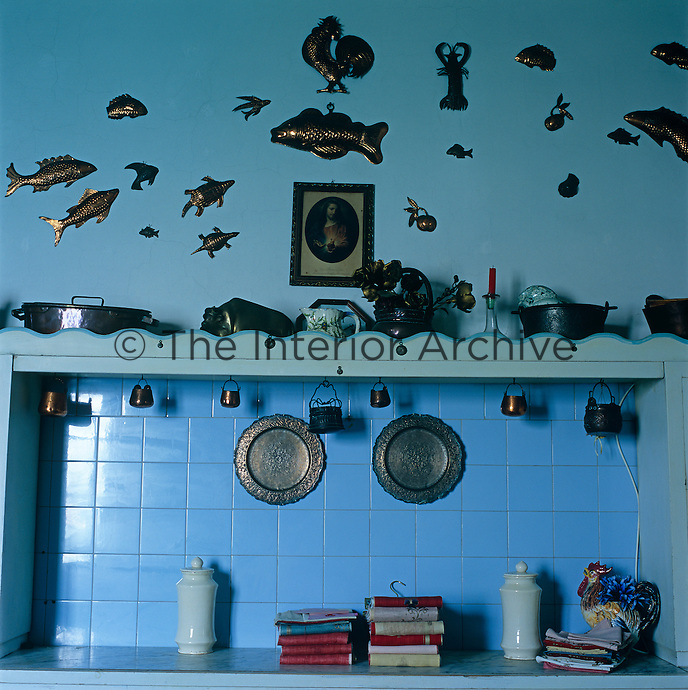 A blue wall of the kitchen is decorated with copper jelly moulds of fish and fruit