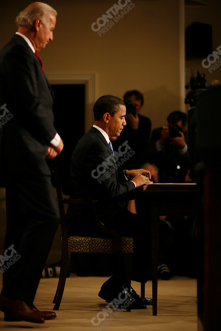 President Barack Obama signs his first executive orders allowing greater transparency in government and capping pay for senior White House staff. Vice-President Joe Biden looks on. Executive Office Building, Washington D.C., January 21, 2009