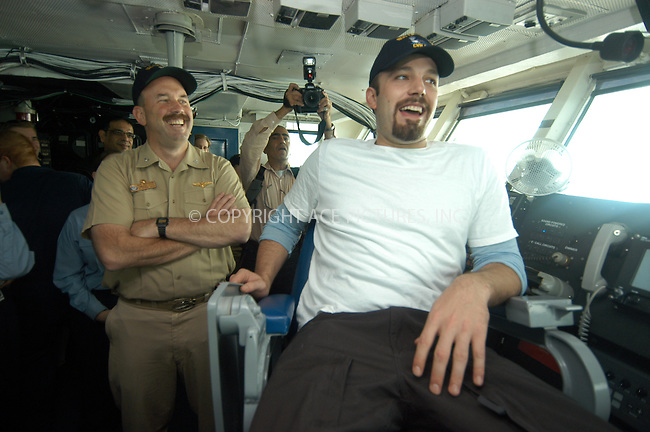Bahrain (Dec. 22, 2003) -- Aboard USS Enterprise (CVN 65), Commanding Officer Capt. Eric C. Neidlinger, left, shares a laugh with Academy Award winning actor Ben Affleck, who enjoys the view from the Captain's chair during a tour of the ship's bridge. Affleck was aboard the nuclear powered aircraft carrier kicking off a United Service Organization (USO) sponsored tour of the Arabian Gulf. U.S. ....Ref: TVSL0001. NY Photo Press does not claim any Copyright or License in the attached material. The attached material intended for reference or research. By publishing this material, the user expressly agrees to indemnify and to hold NY Photo Press harmless from any claims, demands, or causes of action arising out of or connected in any way with user's publication of the material.....NY Photo Press:  ..phone (646) 267-6913;   ..e-mail: info@nyphotopress.com