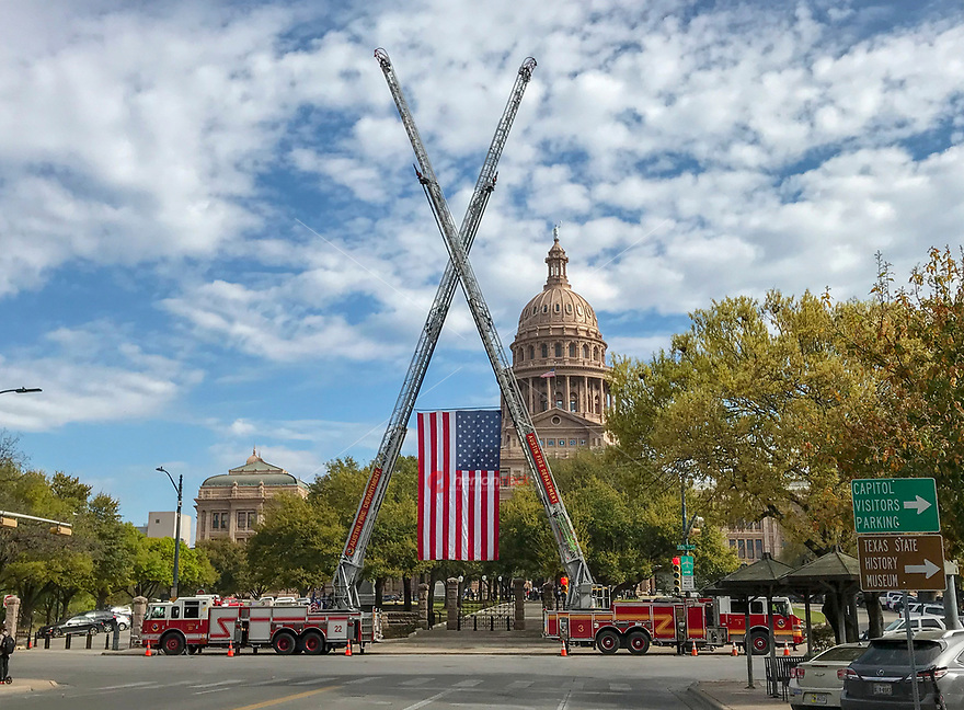 "In Austin patriotism shines bright as ""old glory,"" the US flag, is hoisted by cranes on the Austin Fire Department fire engines at the Texas State Capitol in the heart of downtown Austin, Texas."